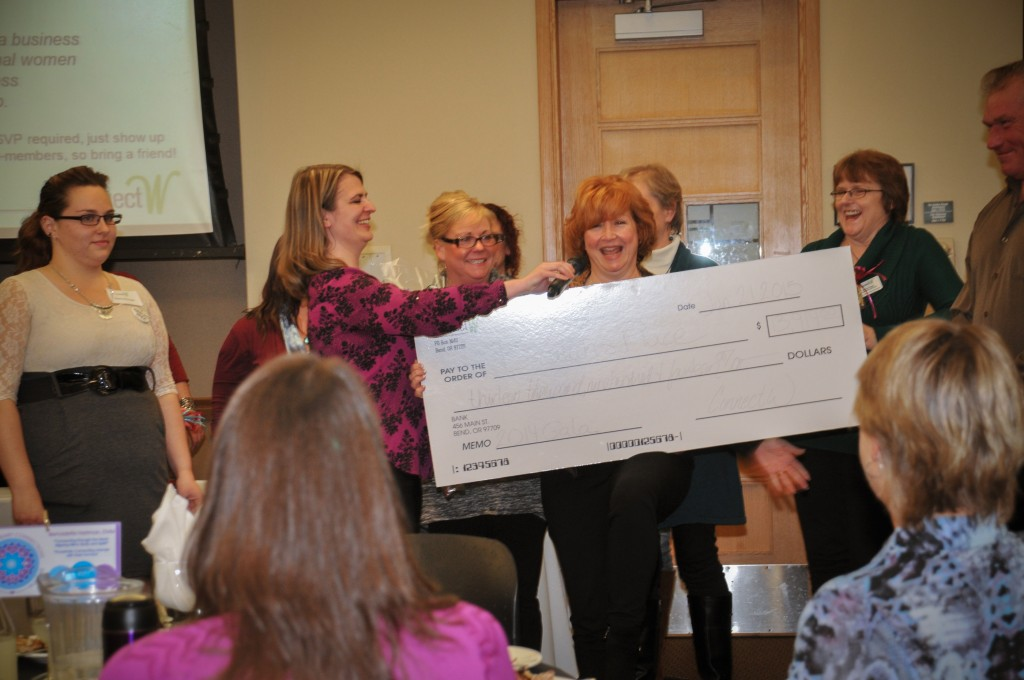 ConnectW Events Chair Amanda Albrich presents check to Beulah's Place Andi Buerger